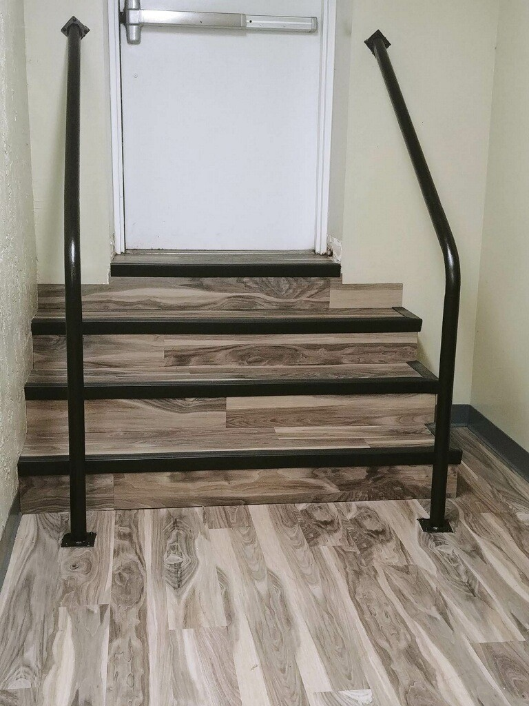 stairs leading to exit door with wood grain floors